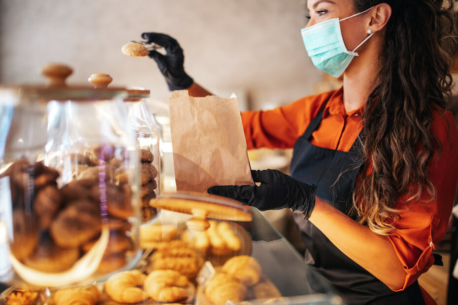 Shutterstock: Woman in mask putting baked treat into bag