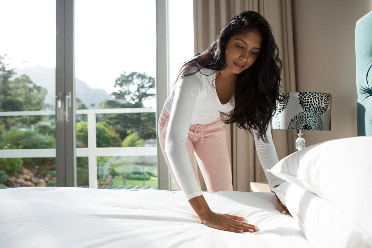 Shutterstock: Woman making clean white bed