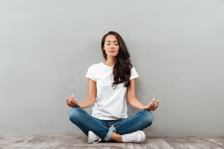 Shutterstock: Woman meditating against grey wall