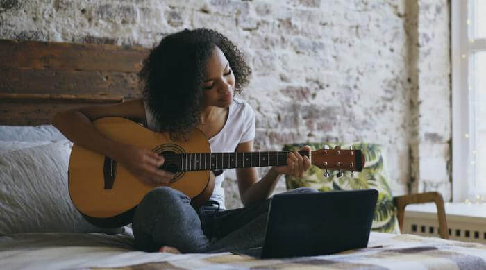 Shutterstock: Woman playing guitar on bed