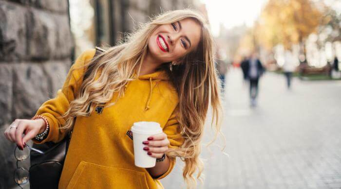 Shutterstock: smiling blonde woman wearing an orange sweater