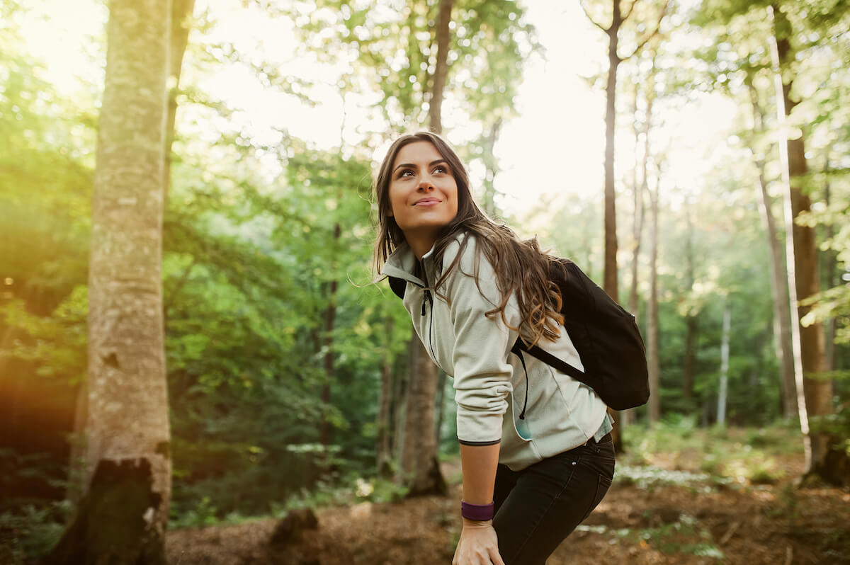 Shutterstock: Woman with backpack smiling in nature with trees forest