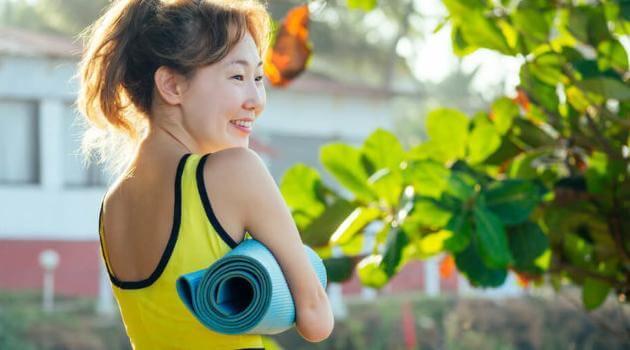 Shutterstock: woman holding a yoga mat
