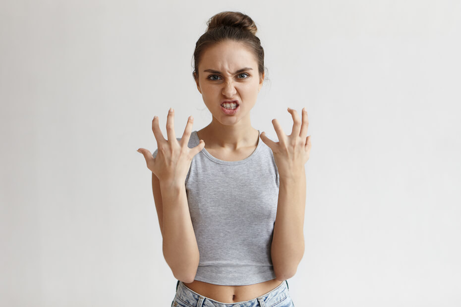 Shutterstock: Picture of enraged dissatisfied young female grimacing, clenching teeth and making angry gesture while feeling furious at her cat that broke vase. Negative human emotions, feelings and reaction