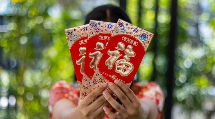Shutterstock: The Chinese sentence means' Happy, fortune, good luck, satisfying all desires ' It is a blessing on envelopes that we will find in every Chinese New Year. The young girl held many red envelopes.