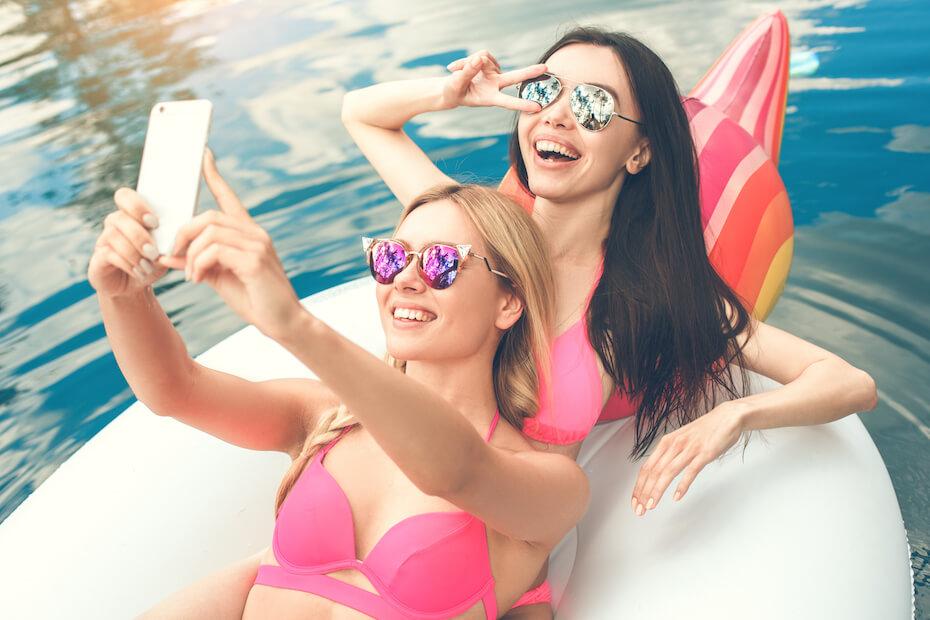 Shutterstock: Young women friends in the swimming pool fun
