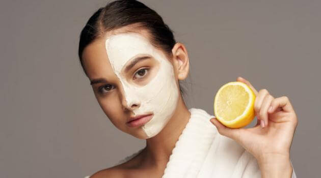 Shutterstock: woman holding a lemon and wearing a face mask