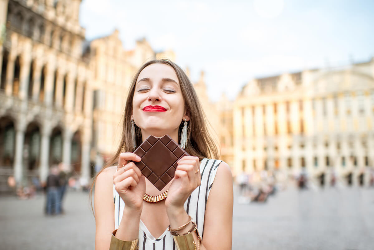 Shutterstock: Young and happy woman with dark chocolate bar standing outdoors on the Grand place in Brussels in Belgium. Belgium is famous of its chocolate
