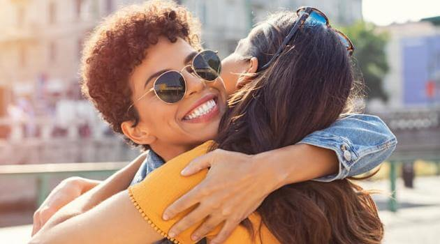 Shutterstock: woman smiling while hugging friend