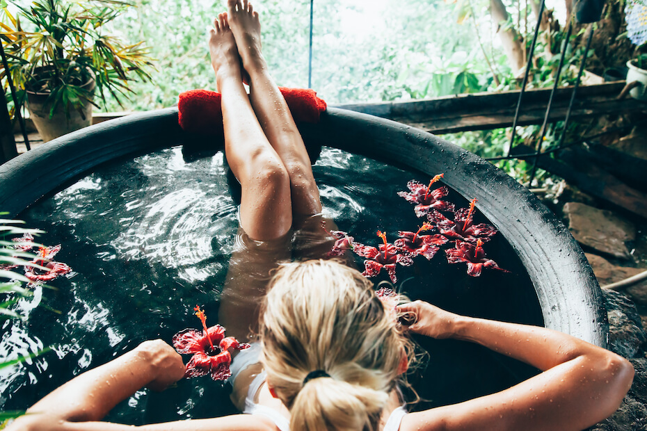 Shutterstock: Woman relaxing in round outdoor bath with tropical flowers. Organic skin care in kawa hot bath in luxury spa resort.