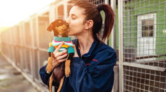 Shutterstock: woman holding dog in dog shelter