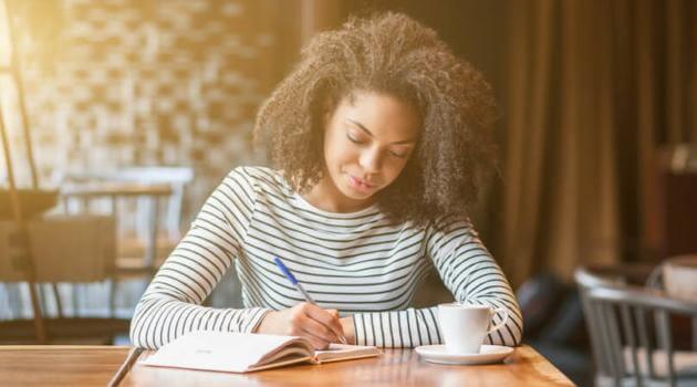 Shutterstock: woman journaling in a coffee shop