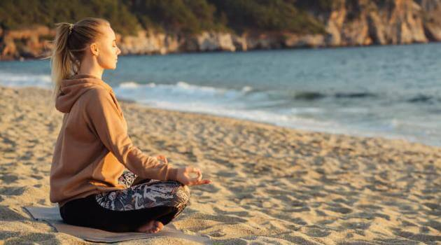 Shutterstock: woman meditating at the beach by the ocean
