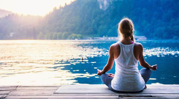 Shutterstock: Young woman meditating by the lake