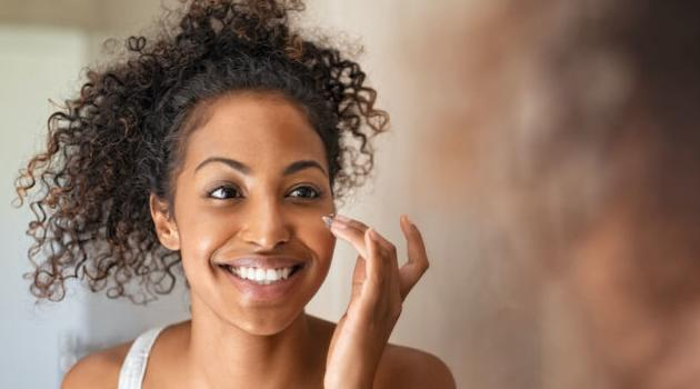 Shutterstock: woman putting on a skincare product and looking in mirror
