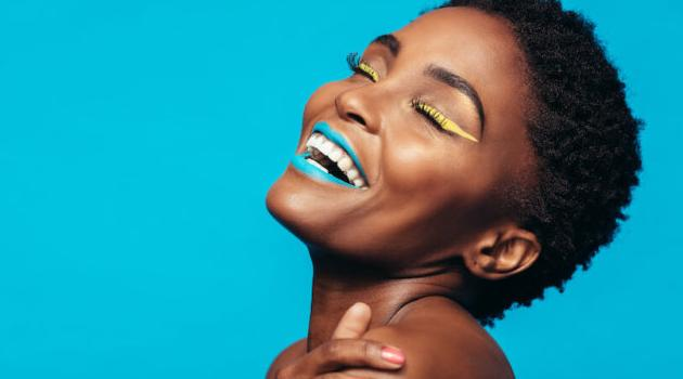 Shutterstock: woman smiling in front of blue background