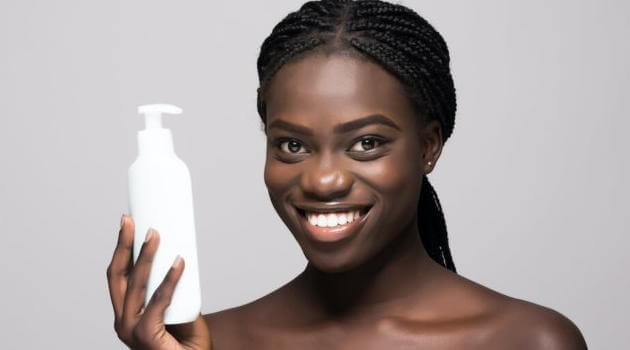 Shutterstock: woman smiling and holding up skincare product