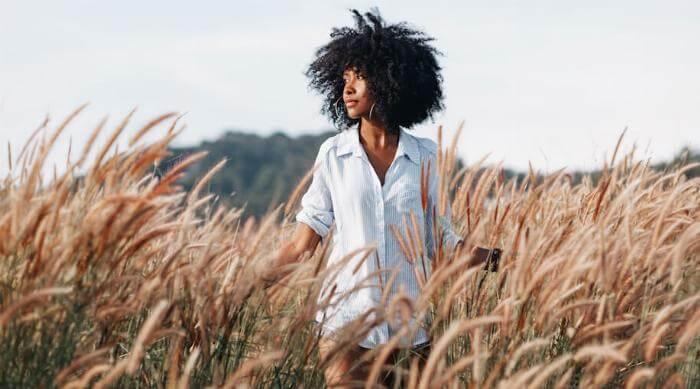 Shutterstock: Woman waking through wheat field outdoors sunny