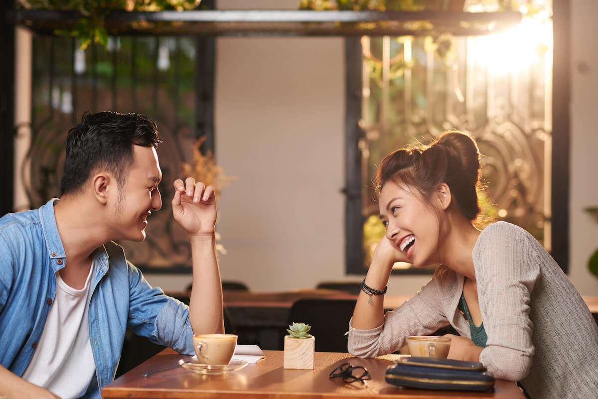 Shutterstock: Side view portrait of laughing Asian couple enjoying date in cafe