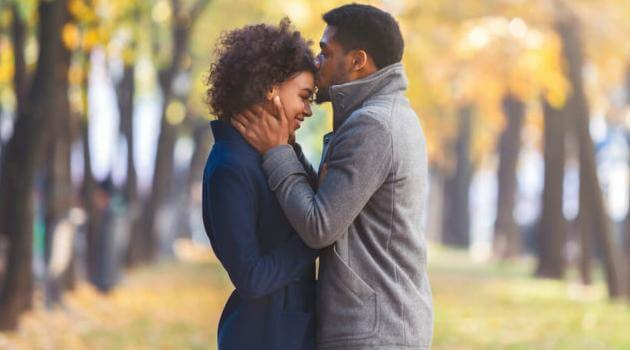 Shutterstock: man kissing woman's forehead while standing outside