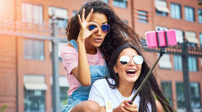 Shutterstock: Two smiling young girlfriends sitting on a city bench making faces while taking self portraits together with a smartphone and selfie stick