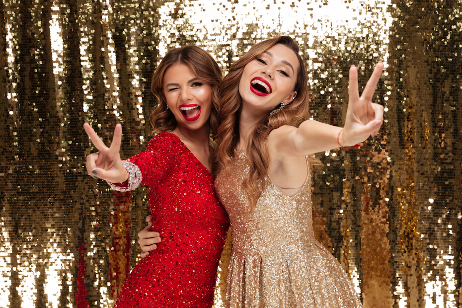 Shutterstock: Portrait of two excited cheery women in sparkly dresses showing peace gesture and winking wile standing and posing isolated over golden shiny background