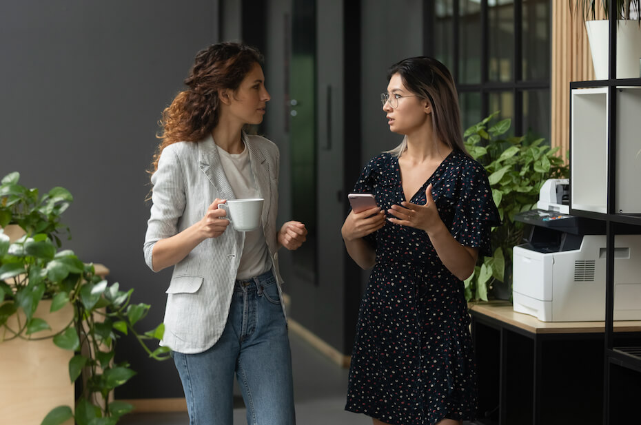 Shutterstock: Two multicultural female colleagues enjoying coffee break time, discussing working issues during walk at office. Young vietnamese intern consulting with caucasian female leader at coworking workplace.