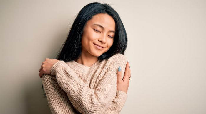 Shutterstock: Young beautiful chinese woman wearing casual sweater over isolated white background Hugging oneself happy and positive, smiling confident. Self love and self care