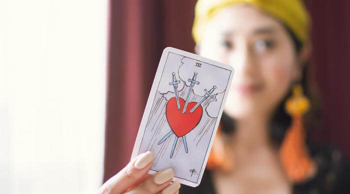 Shutterstock: Bangkok, Thailand on 21 July 2019 - Closeup to a tarot card of heart stabbed by three swords, blur focus of gypsy woman
