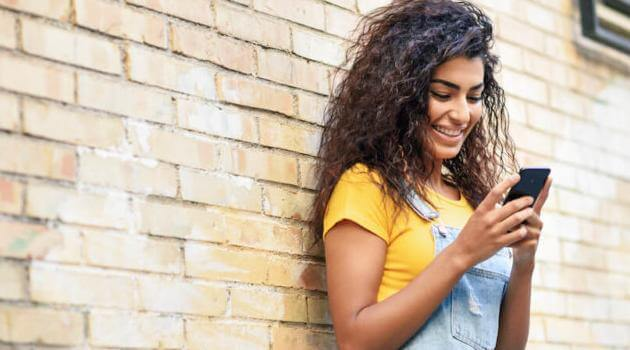 Shutterstock: woman looking at phone and standing in front of brick wall
