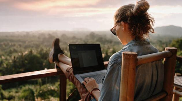 Shutterstock: woman on balcony while on her computer
