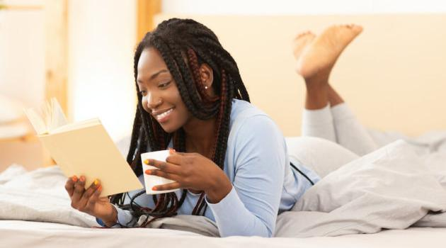 Shutterstock: woman reading on a bed