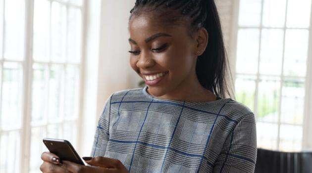 Shutterstock: woman smiling and looking at her phone