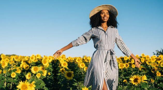 Shutterstock: woman walking through sunflower field