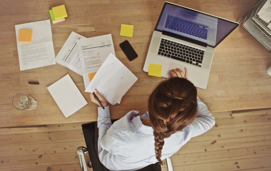 Shutterstock: High angle view of an young brunette working at her office desk with documents and laptop. Businesswoman working on paperwork.