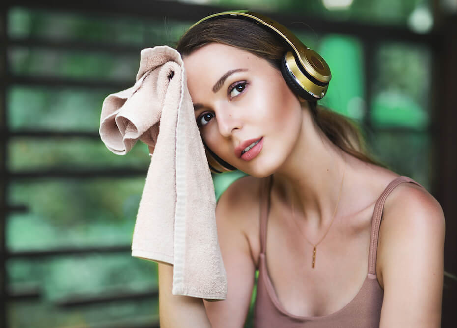 Shutterstock: Lifestyle portrait of pretty young sporty woman resting after sports training. Tired and exhausted. Wiping the sweat with a towel. Wearing stylish sportswear top, headphones. Resting after fitness