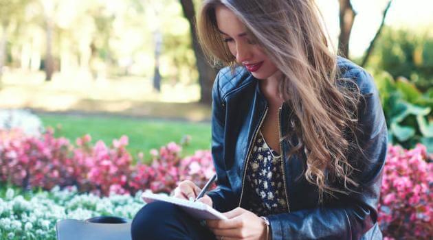 Shutterstock: woman writing in a notebook outside