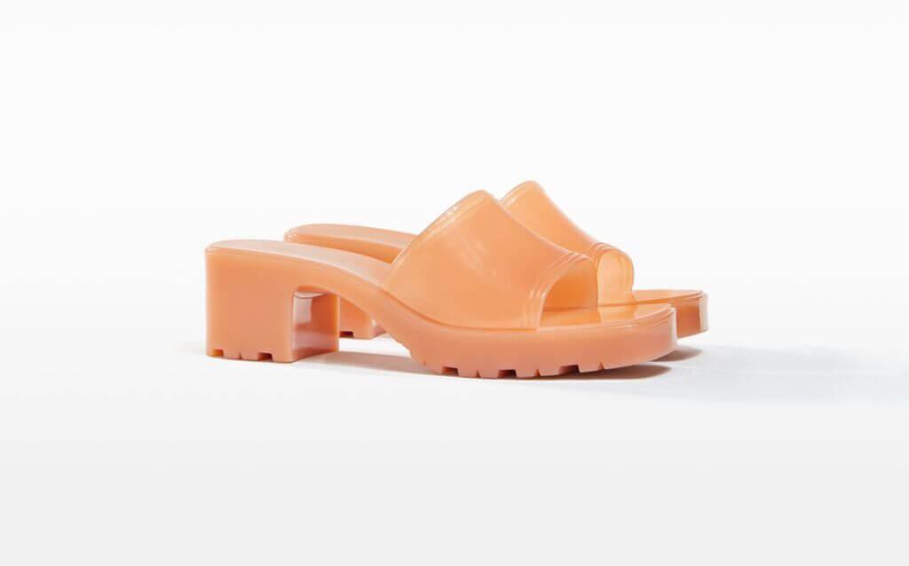 A salmon orange heel sandals with a white background