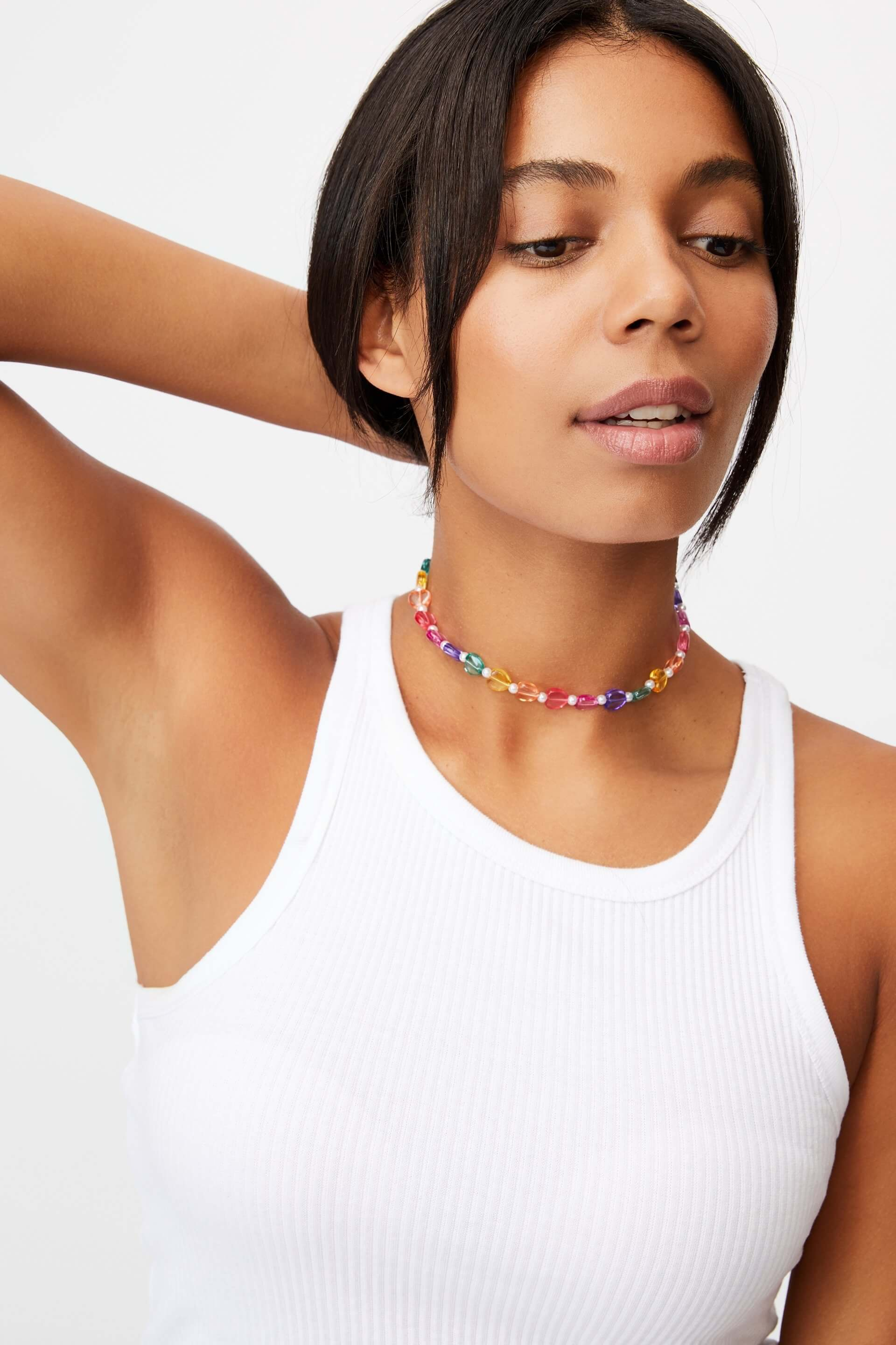 a girl wearing a beaded necklace by cotton on