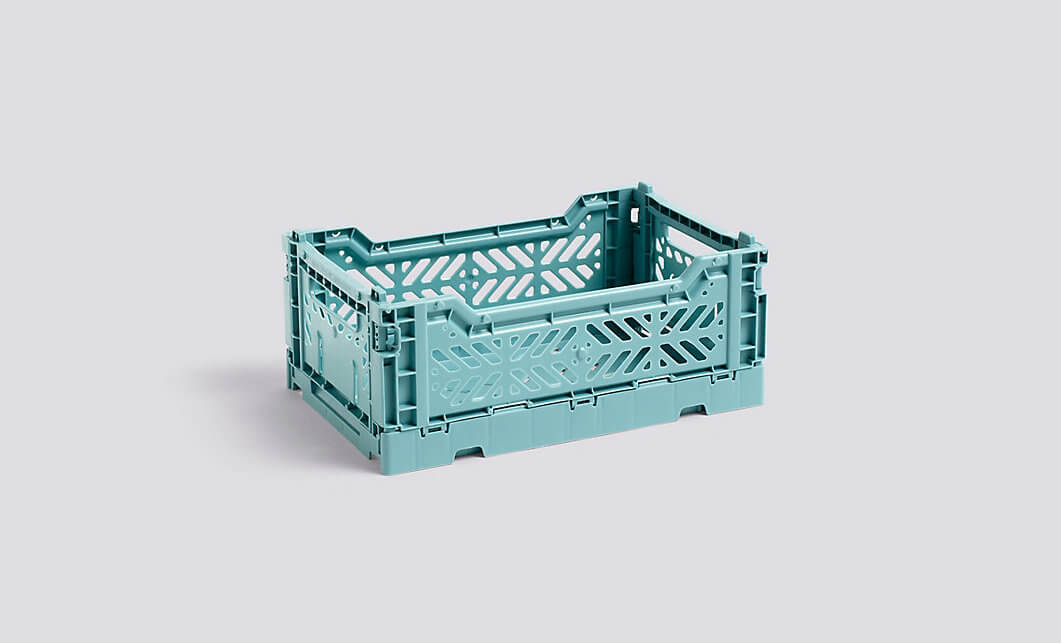 blue plastic crate on a white background by hay