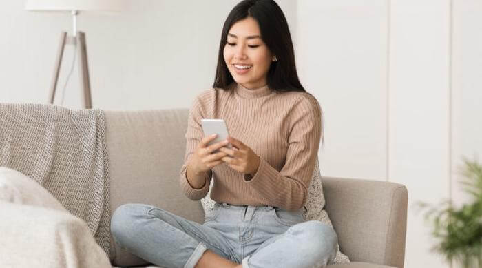 Shutterstock: woman on her phone sitting on couch