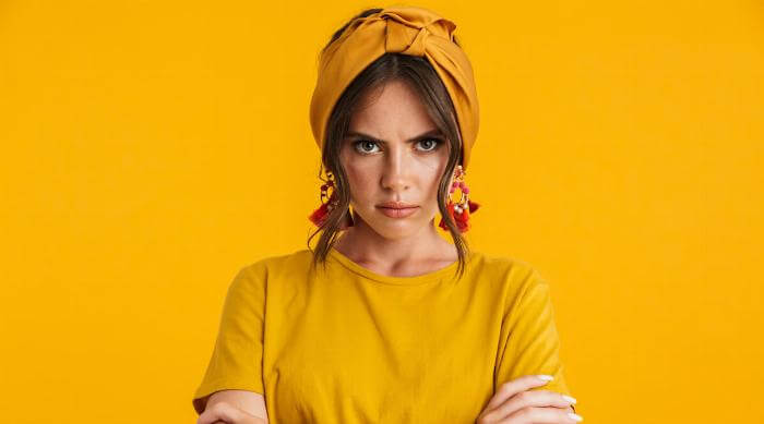Shutterstock: woman looking angry in front of yellow wall