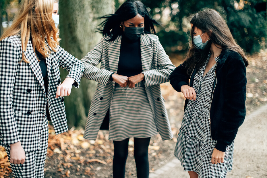 Shutterstock: three women wearing face masks greeting with elbow bump. Elbow bumping is a new normal safety rule for preventing the spread of coronavirus. Social distancing and friendship concept.