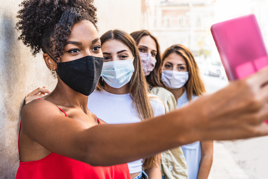 Shutterstock: Four young multiracial friends women with face mask for protection by infection from Coronavirus, Covid-19 - Millennials taking a selfie with smartphone