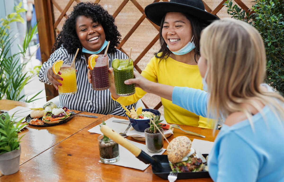 Shutterstock: Multiracial girls have fun at brunch bar and cheering with smoothies while wearing surgical face masks under chin - Coronavirus lifestyle