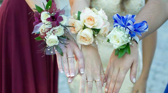 Shutterstock: Three girls showing off prom corsages in photo