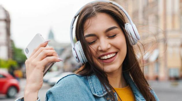 Shutterstock: woman listening to music, holding phone and wearing wireless headphones