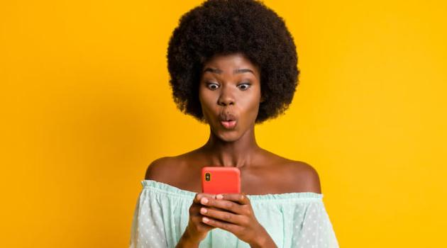 Shutterstock: woman looking at phone shocked in front of bright yellow background