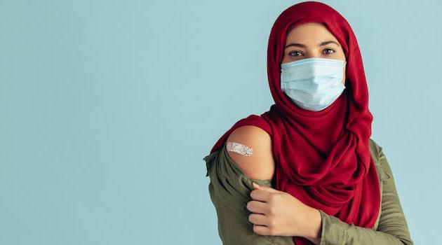 Shutterstock: woman wearing face mask and showing band-aid from vaccine