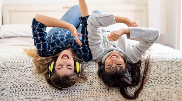 Shutterstock: COVID-19 lockdown. Confident and optimistic women best girlfriends laughing listening online music singing and dancing together in bed at home in isolation. Stay home safe health and safety campaign.